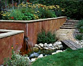 PETERSFIELD GARDEN WOODEN BRIDGE OVER STREAM WITH RENDERED WALL AND WATER FEATURE. DESIGNER: MARK LAURENCE