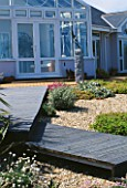 SEASIDE GARDEN  GUERNSEY: THE HOUSE  GRAVEL  WOODEN BOARDWALK AND SEAGULLS SCULPTURE BY GUY PORTELLI