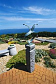 SEASIDE GARDEN  GUERNSEY: VIEW OUT TO SEA WITH BRICK PATIO  GRAVEL  CHINESE GRANITE SEAT  AND SEAGULLS SCULPTURE BY GUY PORTELLI
