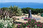 SEASIDE GARDEN  GUERNSEY: VIEW OUT TO SEA AND THE ISLAND OF SARK WITH GRAVEL GARDEN  SLATE WATER FEATURE  CENTRANTHUS ALBA  THRIFT AND PHORMIUMS