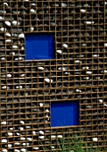 WESTONBIRT INTERNATIONAL FESTIVAL OF GARDENS  2003: SITUATION BY ANDY STURGEON: PEBBLE AND MESH WALL WITH BLUE PERSPEX