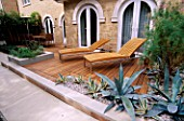 WOOD AND LIMESTONE TERRACE BESIDE HOUSE WITH SUN LOUNGERS  TAMARIX  AGAVE AMERICANA AND AGAVE AMERICANA VARIEGATA.  DESIGN : AMIR SCHLEZINGER/ MY LANDSCAPES