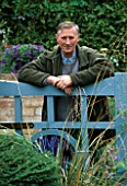 PAUL PICTON LEANS ON THE GATE AT THE PICTON GARDEN  WORCESTERSHIRE
