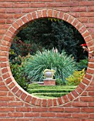 THE BLANKE BOXWOOD GARDEN AT THE MISSOURI BOTANIC GARDEN  ST LOUIS  USA: VIEW THROUGH A BRICK WALL TO AN URN