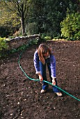 CLARE MATTHEWS USING A HOSE TO LAY OUT A PATH IN HER DEVON GARDEN