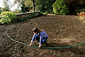 CLARE MATTHEWS USING A HOSE PIPE TO LAY OUT A PATH IN HER DEVON GARDEN
