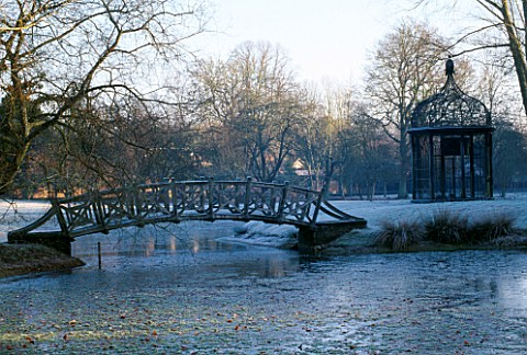 WEST_GREEN_HOUSE_GARDEN__HAMPSHIRE_ORNAMENTAL_BIRD_CAGE_AND_BRIDGE_BESIDE_A_LAKE_IN_THE_NEOCLASSICAL