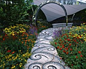 CHELSEA FLOWER SHOW 2004: LIFE GARDEN DESIGNED BY JANE HUDSON AND ERIK DE MAEIJER: PEBBLE MOSAIC PATH BY MAGGY HOWARTH LEADS TO SEAT  TENSILE FABRIC CANOPY AND HOT PLANTING