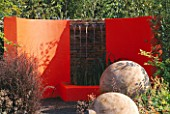 CHELSEA 2004: THE MERGER GARDEN DESIGNED BY ANDREW DUFF: SEMI CIRCULAR ORANGE RENDERED WALL AND WATER FEATURE WITH LARGE POPLAR SPHERES CUT FROM TREE STUMPS