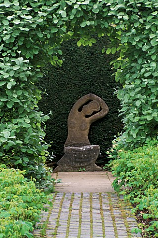 KIFTSGATE_COURT__GLOUCESTERSHIRE_STONE_SEAT_STATUE_BY_SIMON_VERITY_FRAMED_BY_CLIPPED_SORBUS_ARIA_LUT