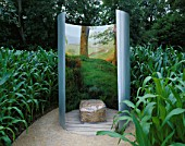 STRAW BALE SEAT SURROUNDED BY CURVED STAINLESS STEEL SCREEN LINED WITH PHOTOGRAPH IN SOMETHINGS WILL NOT GROW GARDEN AT WESTONBIRT2004. DESIGNER: LESLEY KENNEDY