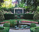 AMSTERDAM: PRIVATE GARDEN WITH BOX HEDGING  SUMMERHOUSE  CLIPPED HOLLIES  BEDDING BEGONIAS  POOL AND CUPID WATER FOUNTAIN