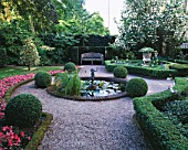 AMSTERDAM: PRIVATE GARDEN WITH BOX HEDGING  CLIPPED HOLLIES  BEDDING BEGONIAS  POOL AND CUPID WATER FOUNTAIN  STONE URN AND WOODEN BENCH