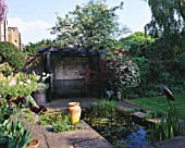 DESIGNER: SHEILA STEDMAN - RECTANGULAR POOL  BLACK TIMBERED ARBOUR AND SEAT  STORK SCULPTURE AND ACER IN A POT