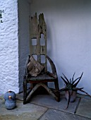 DESIGNER: CLARE MATTHEWS - DEVON GARDEN - WOODEN THRONE CHAIR WITH CUSHION IN THE PORCH WITH GRANITE CANDLES