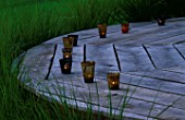 DESIGNER CLARE MATTHEWS: THE DECK CHAIR AT DUSK WITH CANDLES  SURROUNDED BY STIPA ARUNDINACEA