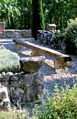 LA CHABAUDE  FRANCE. DESIGNER - PHILIPPE COTTET: A PLACE TO SIT - GRAVEL TERRACE WITH LONG WOODEN BENCH PROPPED UP BY STONE BLOCKS  STONE WALL AND CYPRESS TREE