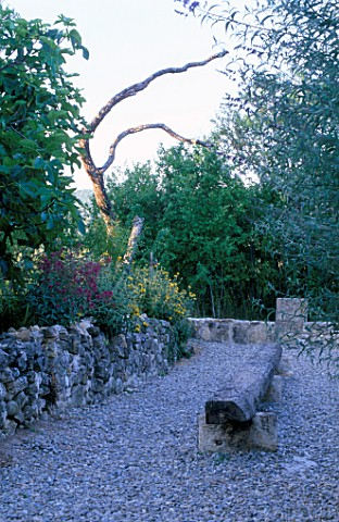 LA_CHABAUDE__FRANCE_DESIGNER__PHILIPPE_COTTET_GRAVEL_TERRACE_WITH_LARGE_WOODEN_LOG_SEAT__STONE_WALL_