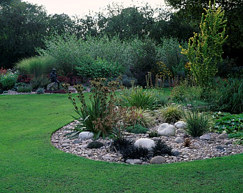 GRAVEL_BORDER_BESIDE_LAWN_WITH_ERYNGIUM_AGAVIFOLIUM__ROCKS_AND_OPHIOPOGON__DESIGNER_JOHN_MASSEY