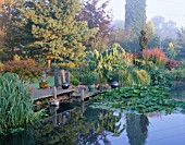 VIEW ACROSS THE LILY POND WITH A WOODEN PONTOON  ROCK SCULPTURES AND AN AGAVE IN A CONTAINER. DESIGNER: JOHN MASSEY