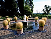 PARSONAGE  OMBERSLEY  WORCESTERSHIRE: PARTERRE ON OLD TENNIS COURT WITH TERRACOTTA CONTAINERS PLANTED WITH STIPA TENUISSIMA AROUND A WATER SPOUT