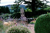 DESIGNER CLARE MATTHEWS: DEVON GARDEN WITH GRAVEL  WOODEN THRONE CHAIR  ERIGERON  STIPA TENUISSIMA AND VIEWS TO THE BLACKDOWN HILLS