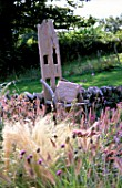 CLARE MATTHEWS GARDEN  DEVON: WOODEN THRONE CHAIR IN THE GRAVEL GARDEN WITH STIPA TENUISSIMA IN THE FOREGROUND