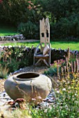WOODEN THRONE CHAIR IN THE GRAVEL GARDEN WITH LARGE URN SITTING ON A RAISED BROKEN SLATE BORDER. CLARE MATTHEWS GARDEN  DEVON.