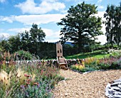 CLARE MATTHEWS GARDEN  DEVON: THE GRAVEL GARDEN  WALL AND WOODEN THRONE CHAIR WITH THE BLACKDOWN HILLS BEHIND