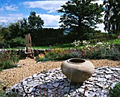CLARE MATTHEWS GARDEN  DEVON: THE GRAVEL GARDEN WITH LARGE URN ON SLATE BORDER AND WOODEN THRONE CHAIR BEHIND