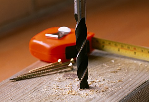 DRILLING_INTO_WOOD_WITH_TAPE_MEASURE_AND_BRASS_SCREWS