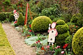 WEST GREEN HOUSE  HAMPSHIRE  SPRING. ALICE IN WONDERLAND CHARACTERS BESIDE BORDER WITH CLIPPED TOPIARY AND TULIPS