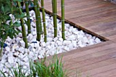 CHUNKS OF LIMESTONE FORM MULCH AROUND BAMBOO STEMS AND DECKING PATHWAY  IN HIS LATE HIGHNESS SHAIKH ZAYED BIN SULTAN AL-NAYHANS GARDEN BY CHRISTOPHER BRADLEY-HOLE. CHELSEA 2005