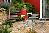 METAL CHAIRS SURROUND CIRCULAR TABLE IN FRONT OF RED WALL ON PATIO (TERRACE). WINGWELL NURSERY   RUTLAND