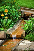 WATER FEATURE: RILL ON DIFFERENT LEVELS WITH PRIMULAS BESIDE. WINGWELL NURSERY   RUTLAND