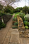 PATH LEADING AWAY FROM THE PATIO TO THE LAWN  WITH A DRYSTONE WALL ON THE RIGHT. WINGWELL NURSERY   RUTLAND