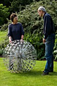 ROSE AND JOHN DEJARDIN ON THE LAWN WITH ALLIUM  A SCULPTURE BY RUTH MOILLIET. WINGWELL NURSERY   RUTLAND