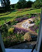 CLARE MATTHEWS GARDEN  DEVON: VIEW ONTO THE GRAVEL GARDEN WITH ERIGERON  NEPETA WALKERS LOW  SLATE  LARGE EMPTY CONTAINER  STIPA TENUISSIMA AND WOODEN THRONE CHAIR