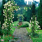 METAL ARBOUR WITH CLIMBING WHITE ROSE ADELAIDE DORLEANS OVER PATH AT LOWER HALL GARDEN  SHROPSHIRE. BRONZE SCULPTURE BY PETER BALL
