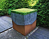 RIDLERS GARDEN  SWANSEA  WALES: LEAD AND RUSTY METAL CONTAINER PLANTED WITH BOX TABLE : DESIGNER: TONY RIDLER