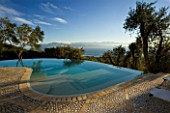 VIEW OF THE ALBANIAN MOUNTAINS WITH  OLIVE TREES AND INFINITY SWIMMING POOL IN THE FOREGROUND: GINA PRICES GARDEN  CORFU