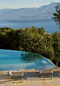 VIEW OF THE ALBANIAN MOUNTAINS WITH  AN OLIVE TREE AND INFINITY SWIMMING POOL IN THE FOREGROUND: GINA PRICES GARDEN  CORFU