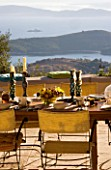 VIEW OVER TABLE WITH FRUIT BOWL TO IONIAN SEA. ISLAND OF CORFU.  GINA PRICES GARDEN