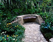 CHELSEA FLOWER SHOW 2005. PAUSE FOR THOUGHT COURTYARD GARDEN  DESIGNERS: LIZ ROBINSON AND PHIL KAYE: DRY STONE WALL WITH RECLAIMED TIMBER SEAT WITH SHADE-LOVING PLANTS