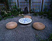 HAMPTON COURT FLOWER SHOW 2005: DESIGNER  LAURA MILBURN. BUDDHIST INSPIRED PEACE GARDEN  MEDITATION  CITY  GRAVEL  THE WHEEL OF DHARMA ON MOSAIC TABLE  LOW MEDITATION STOOLS
