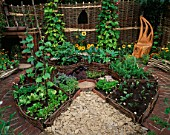 HAMPTON COURT FLOWER SHOW 2005: A TASTE OF SUSSEX. DESIGNER  SUE HITCHINGS. CIRCULAR POTAGER / VEGETABLE GARDEN WITH WILLOW FENCING