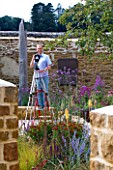 CLIVE NICHOLS ON A STEP LADDER IN HIS GARDEN WITH CAMERAS