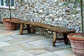 WOODEN BENCH BESIDE FLINT WALL ON THE TERRACE IN CLARE MATTHEWS GARDEN  DEVON