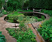 WINGWELL NURSERY  RUTLAND: RILL SPILLS INTO CIRCULAR POOL (POND) WITH STONE SEAT AND WATER SCULPTURE NEW MOON BY GEORGE CUTTS