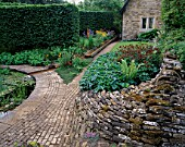 WINGWELL NURSERY  RUTLAND: VIEW TOWARDS THE HOUSE WITH STONE WALL AND PAVING  RILL  ASTRANTIAS AND FERNS